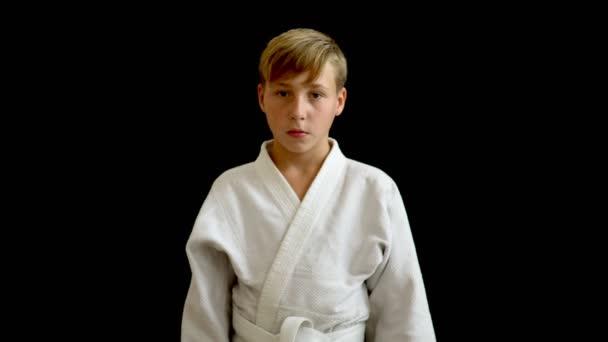 A fehér kimonó egy fiatal sportoló áll egy sötét háttér. Kezében egy fiatalember megy le, ő szőke haj és sötét szemek, egy európai megjelenés.