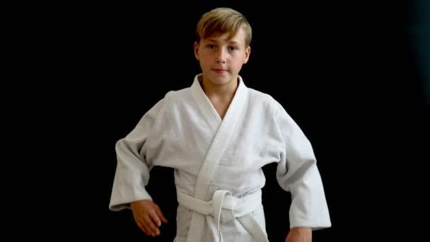 Egy fiatal sportoló mozgásban van. Egy fiatal férfi-egy fehér kimonó csepp kezével végig a testet, ő áll a sötét háttéren, szőke haj.