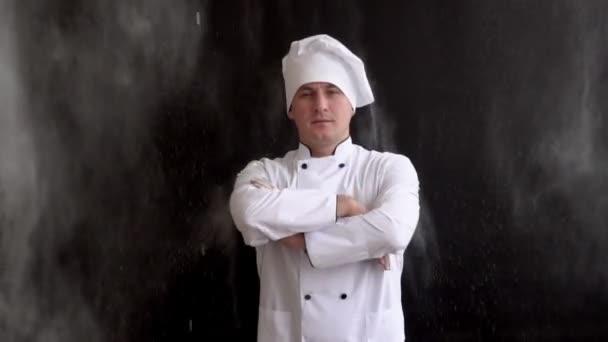 Erwachsener Koch in weißem Anzug und Mütze auf dunklem Hintergrund
