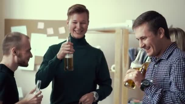 a group of friends in the office drinking alcoholic beverages. Bottled beer. Adults drink beer and clink