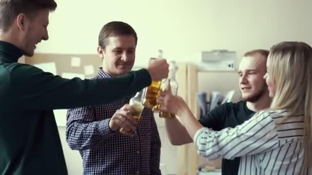 eine Gruppe von Freunden im Büro, die alkoholische Getränke trinken. Flaschenbier. Erwachsene trinken Bier und klirren