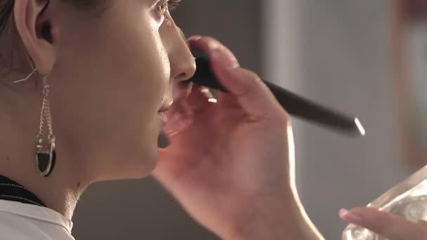 Kozmetikai kozmetikai eljárások. Alkalmazása a szemhéjpúder ecset női szem, nő elhelyezés árnyék por, a szemét, sminkes alkotják a színpadon.