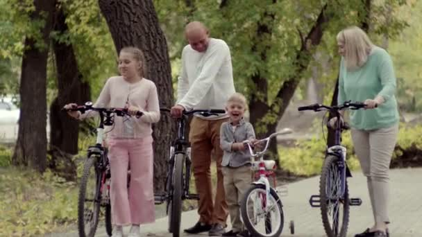 Authentic happy family resting in a Park with a baby boy on the bike. early autumn in the Park lifestyle. Family holidays on bikes