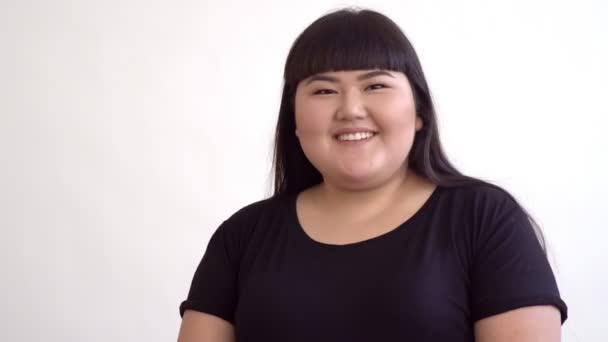 gyönyörű fiatal ázsiai lány a fehér háttér előtt mosolyogva túlsúlyos. Boldog hiteles nő