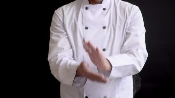 felnőtt férfi szakács öltönyt kopogtat a kezét a lisztből. Lassú mozgás a részecskék Liszt