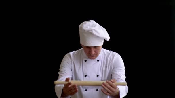 Erwachsener Koch im Anzug reicht Nudelholz als Symbol der Machtübergabe.