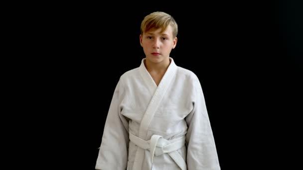 Egy fiú, egy fehér kimonó áll, egy sötét háttér. Keze alá, a fiú a szőke haj, sötét szem, és a derék egy fehér övet.
