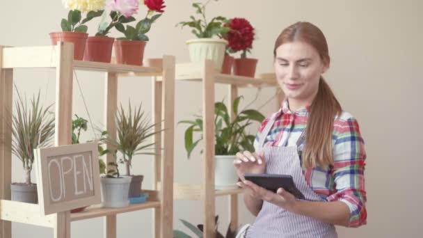 Malé firmy. Dívka v kostkované košili a pruhovanou zástěru stojí s digitálním tabletu v ruce a plány. Květinářství, práce s květinami v květináčích, které jsou na pult. Dívka se dívá na