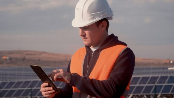 a man in a helmet engineer on the background of a solar power plant holding a digital tablet