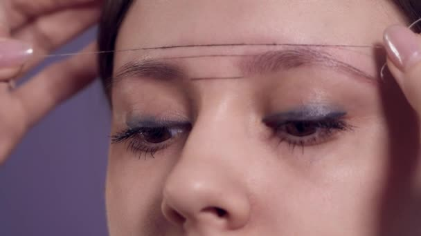 drawing contours on the eyebrows of a woman for applying permanent makeup in a beauty salon