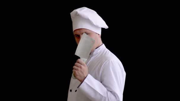 Cook maniak s kuchyní sekeru v ruce vypadá hrozivě na kameru na černém pozadí.