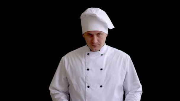 Koch mit wütendem Gesicht in weinroter Uniform zeigt Besteck. Koch präsentiert Geschirr. Restaurantgastronomie. Mann hält Löffel auf schwarzem Hintergrund.
