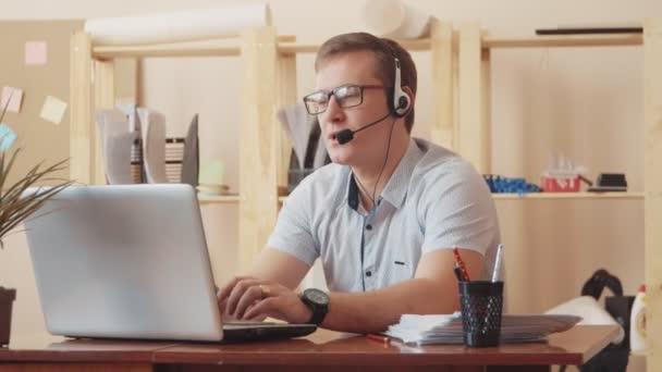 Portrét jistý mužského oddělení služeb zákazníkům s mikrofonem v call-centru. Člověk sedí u počítače a mluví na sluchátka s klientem, Žena přijde k němu a popisuje