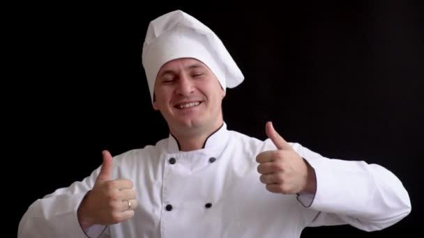 Dospělý samec kuchař v bílém obleku vykazuje známky chuti. vaříme na černém pozadí