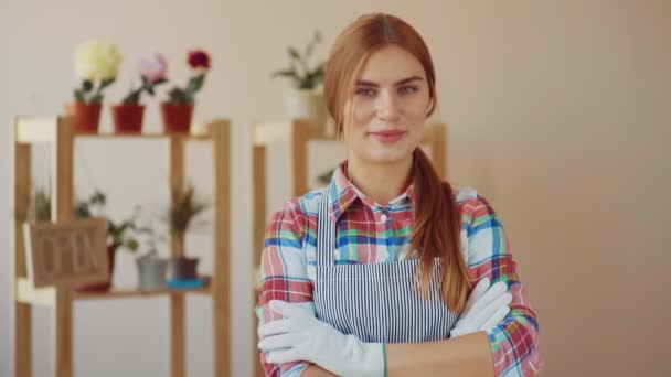 Small business. A girl in a striped apron and plaid shirt stands in a flower shop. The florist girl stands near the shelf with flowers and smiles, pressing her hands to each other, then folds them on