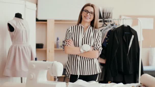 Porträt einer glücklichen schönen Näherin im Atelier. das Mädchen lächelt und blickt in die Kamera