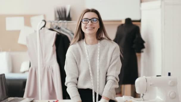 S úsměvem kavkazské bruneta švadlena v ateliéru při pohledu na fotoaparát a směje se.