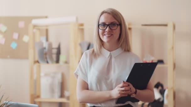 Obchodní lady při pohledu na fotoaparát a směje se