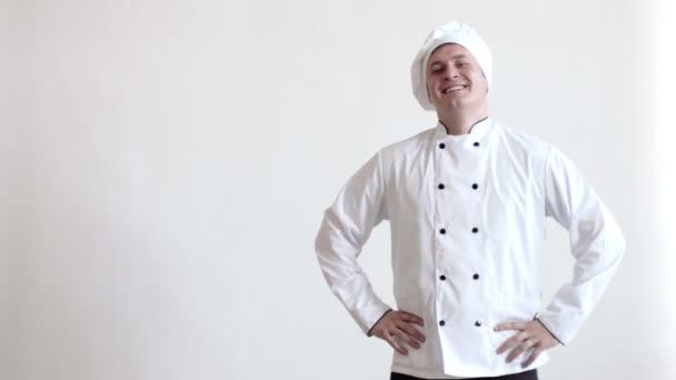 Koch hält Hände am Gürtel, lacht in die Kamera und verschränkt dann die Arme auf der Brust