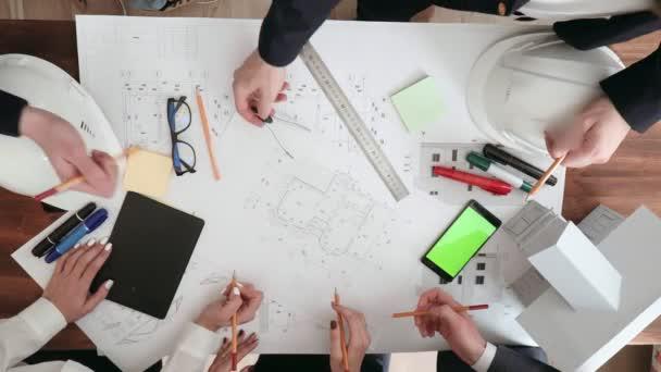Skupina lidí aktivně diskutovat a kontrolu velkých výkresů budovy, na stole jsou brýle, značky, telefon, rozložení, pravítka a kompas.
