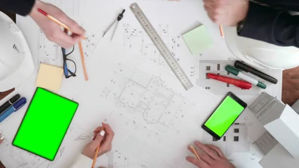 a group of people, closeup discuss and finalize pencils drawing space on the table is a tablet and phone.