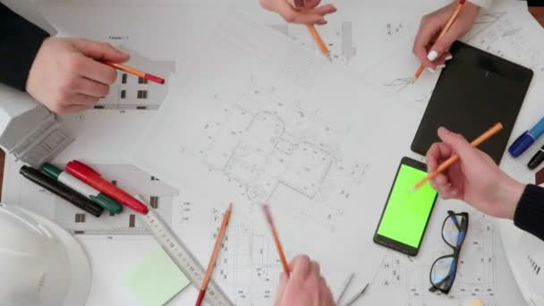 a group of engineers with pencils in their hands discussing the drawing, put pencils on the table and leave. The view from the top on their hands, glasses, building plan and a phone with a green