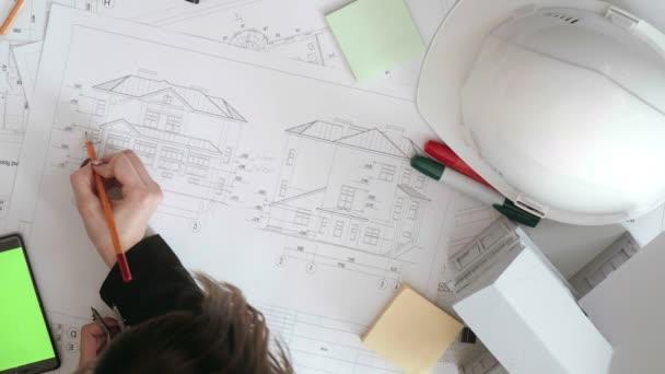 das Mädchen ändert die Größe der Zeichnungen und überprüft sie erneut.