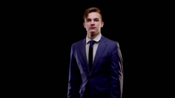 A young man of Caucasian appearance in a simple blue suit with a blue tie with horror grabs his head and yells loudly in the camera