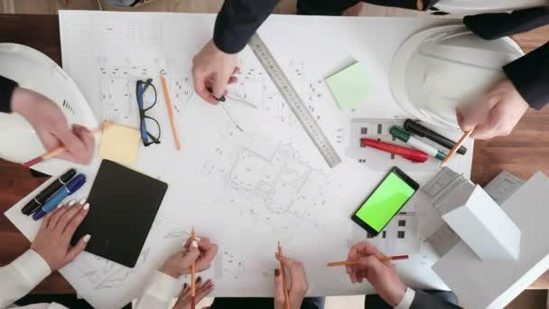 großer Arbeitstisch, auf dem Gläser, Telefon, Filzstifte, Bleistifte, Lineale stehen. Hände der Konstrukteure machen Änderungen an den Zeichnungen