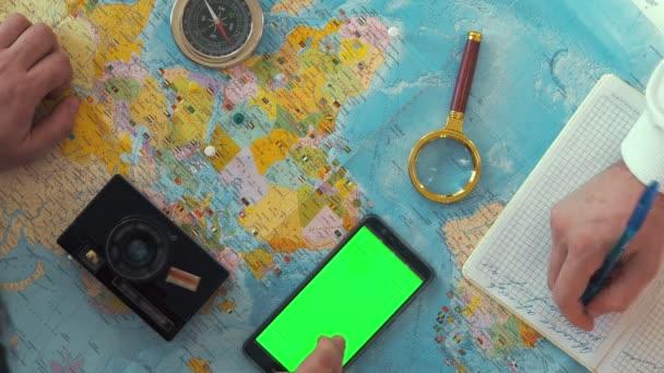 Cestující s lupou studuje svět map a dělat si poznámky poznámkového bloku pro budoucí cestu na stole je kompas, telefon a fotoaparát
