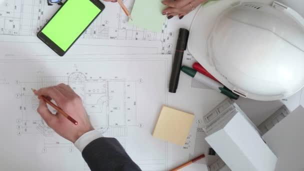 Blick von oben auf die Hände des Ingenieurteams, das die Bauplanung überprüft.