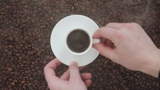 Male hand puts a Cup of coffee with a smoke on a big pile of coffee beans