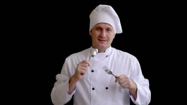 der Koch hält seine Hände mit Löffel und Gabel auf Brusthöhe und beginnt zu klopfen und sich zu bewegen.