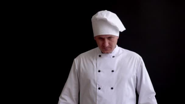vážné cook zvedá ruce s lžící a vidličkou, vypadá vážně do kamery kříže je na úrovni hrudníku.