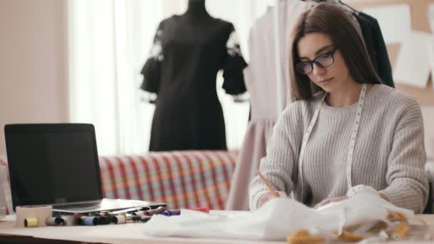 dívka módní návrhář, ve studiu u stolu s hadrem, barevné nitě a notebook, kreslí náčrtek, se podívat na kameru a úsměvy.