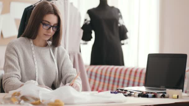 módní návrhář světlé dívka sedí u stolu v Studio a kreslí.