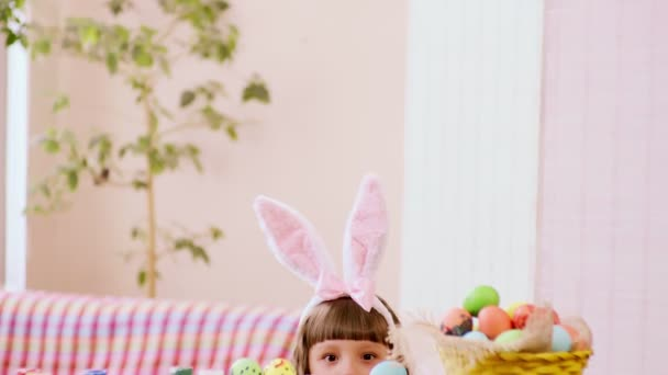 a girl in rabbit ears looks out from behind the table on which stands a basket of Easter eggs.