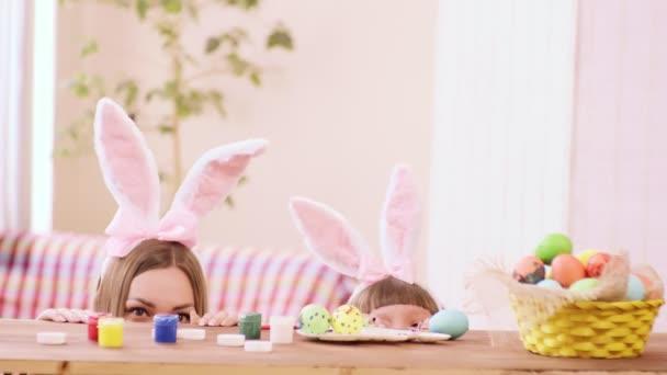 matka a dcera v čelenky s ušima vykukují zpoza stolu a úsměv, na stole jsou barvy a velikonoční vajíčka.