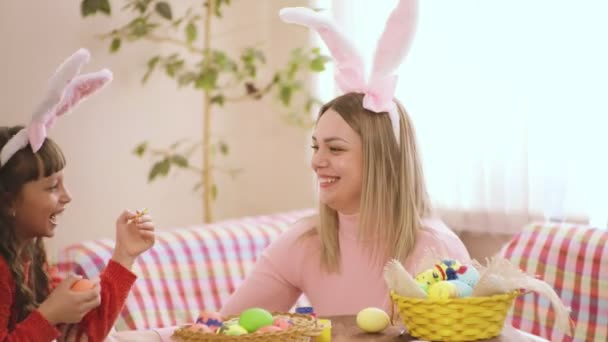 mom and daughter laugh and prepare for Easter.