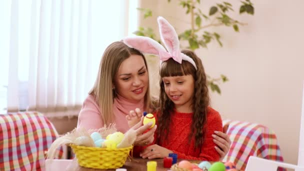 pozor, matka drží velikonoční vajíčko, a její dcera s úsměvem na tváři s prsty máčené v programu Malování vloží značky shell.