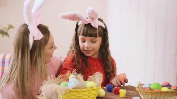 objímání se dívka, při přípravě na Velikonoce, a maminka říká, něco jí do ucha a dívka se směje.