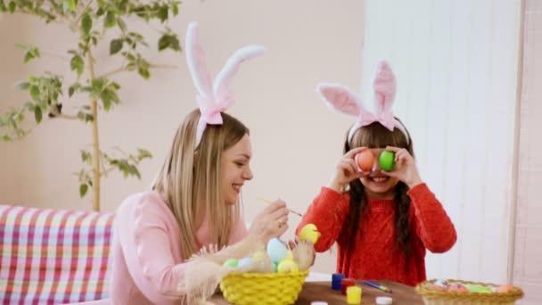 Anya nyúl füle díszíti a húsvéti tojás, és a lánya mellett áll, és rendelkezik a húsvéti tojás, mint a szemét.