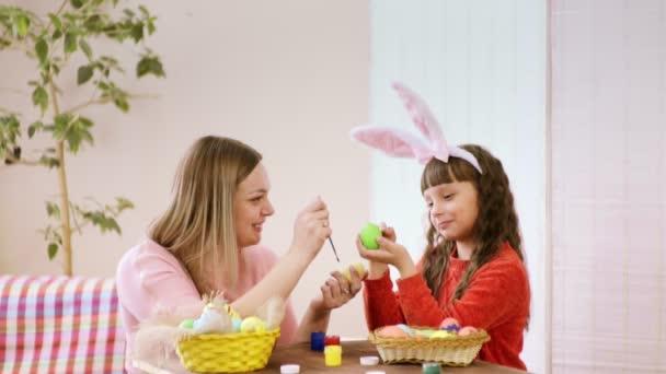 zblízka matku a dceru, která zdobí varlata, dotýkejte se štětců a směje se. Veselé velikonoce.