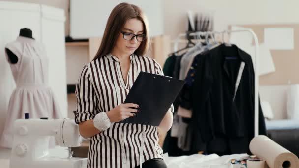 módní návrhářka bere poznámky na papírovou tabletu, zvedá oči a dívá se na usměvavou kameru.