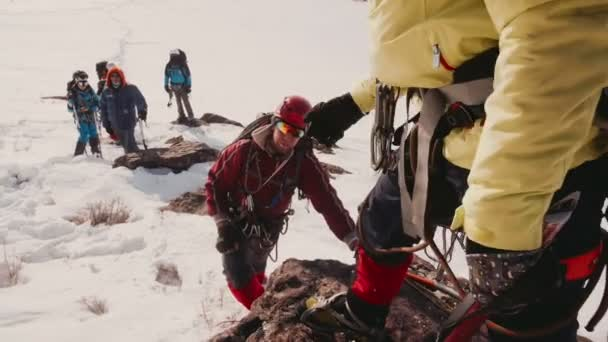 Teammate holds out his hand climbing up the side of the mountain climber, helping him to climb up