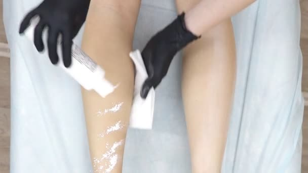 the cosmetologist applies the powder on the womans legs after epilation.