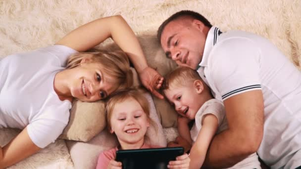 Young family Caucasian appearance on your day off resting lying on the couch and looking at the tablet