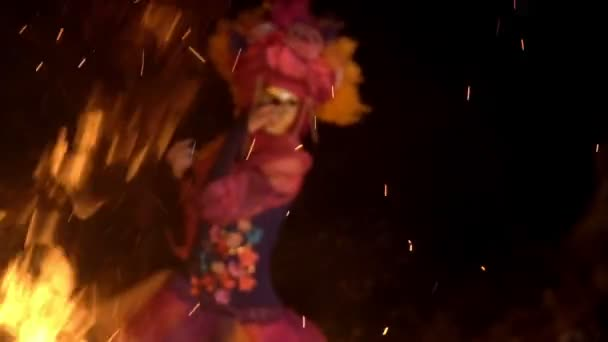 Mystical girl in a bright suit and a gold mask dancing the night by the light of the fire