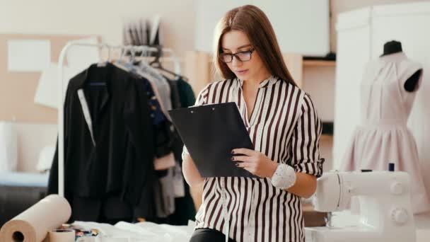 módní návrhářka dělá náčrt v papírovém tabletu a dívá se na kameru s vážnou tváří.
