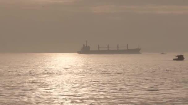Velká nákladní loď stojí na moři osvětleném sluncem, malé lodě kolem ní plují